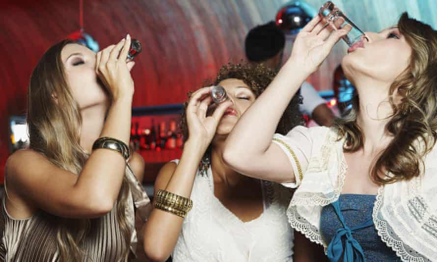 Some women drink some shots in a bar