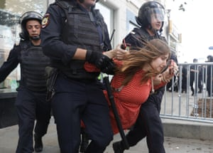 Police officers detain a woman during an unsanctioned rally in the centre of Moscow.