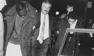 Yusef Salaam, left, is led away by a detective after being arrested in Central Park for allegedly attacking Trisha Meili.