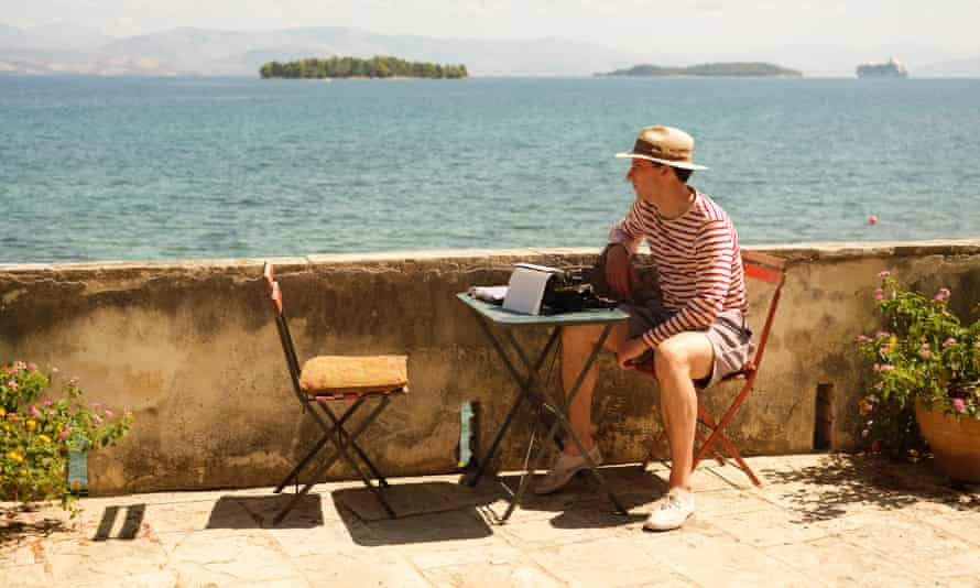 Josh O'Connoll as Larry in the Durrells, sitting at desk with typewriter, overlooking sea