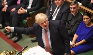 British prime minister Boris Johnson speaking in the House of of Commons, with front bench ministers behind him.