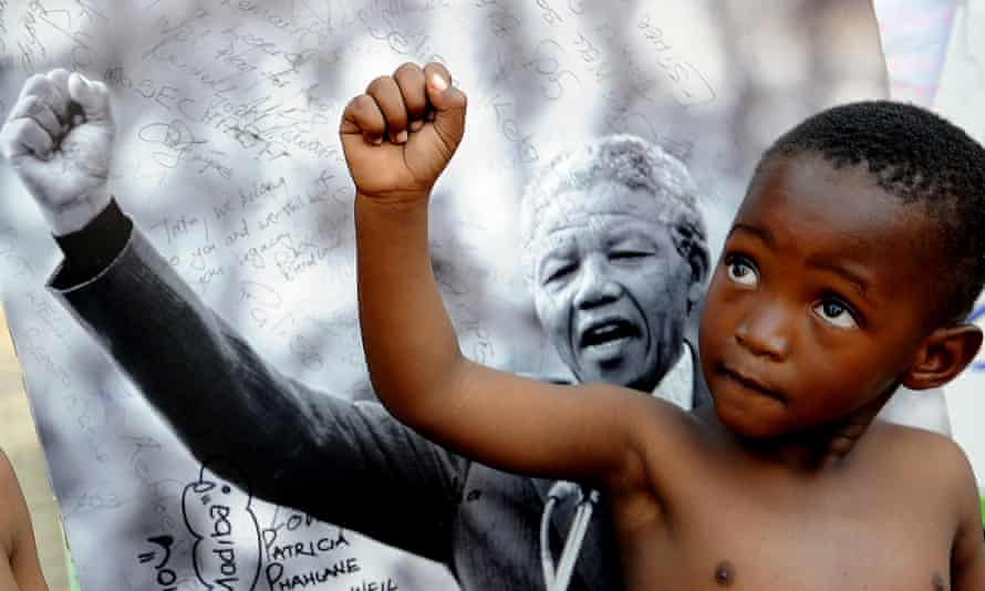 A young member of the Maitibolo Cultural Troupe poses on July 14, 2013 in front of a photograph of former South African President Nelson Mandela in Pretoria. Graca Machel, the widow of Mandela, said the whole continent was in danger of neglecting its youth