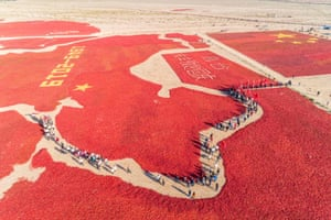 Gansu province, China: Aerial showing people walking amongst an image of a Chinese map and a national flag formed by dried chili peppers during the harvest season in Zhangye