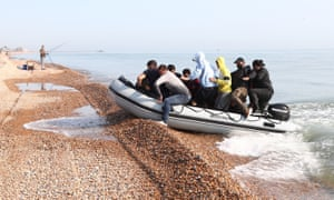 A group of people thought to be migrants arrive in an inflatable boat at Kingsdown beach near Dover after crossing the English Channel.
