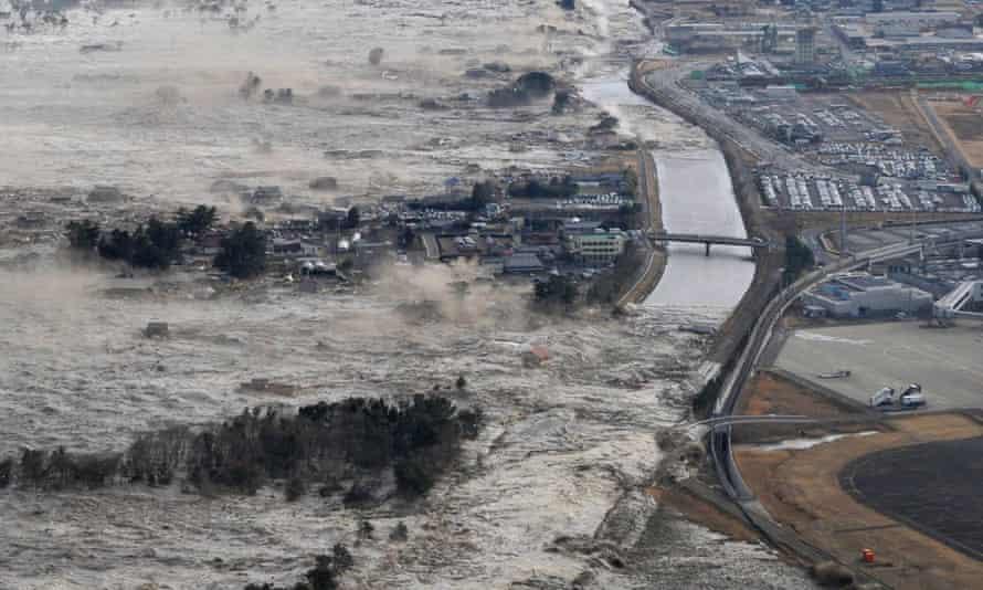 The tsunami sweeps shores along Tohoku.
