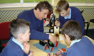 An engineer demonstrating a point to three children