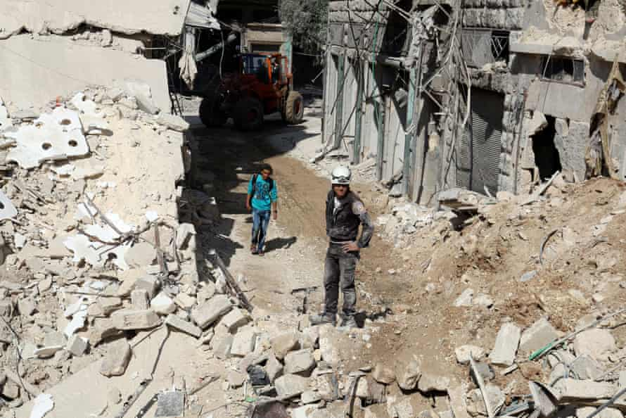 Residents and civil defence staff inspect a site damaged by an airstrike in the rebel-held al-Qaterji neighbourhood.
