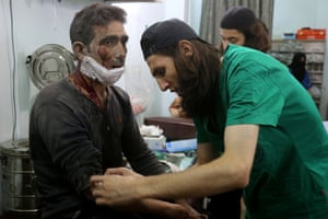 Medics at a makeshift hospital in the Tariq al-Bab district treat a man wounded in an air raid