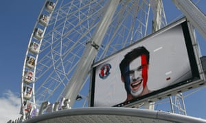 Euro 2016 publicity on the ferris wheel in Paris featuring a supporter with the French flag painted on his face.