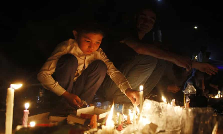 A boy lights a candle during a vigil for victims of a suicide bomb attack in Kabul in 2016