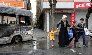 A family walk by a vehicle, which was damaged during the clashes between security forces and Kurdish militants, in Baglar district in the Kurdish-dominated south-eastern city of Diyarbakir.