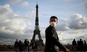 A man wearing a face mask near the Eiffel Tower in Paris.