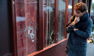 A man looks bullets impacts in the 'Carillon' restaurant, one of the site of the attacks in Paris, the day afte.