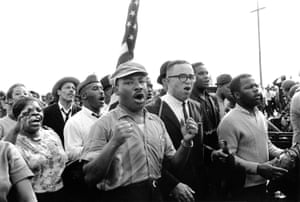 Martin Luther King Jr leads singing marchers towards Montgomery, Alabama, on 21 March 1965. John Lewis, then the chairman of the SNCC, is on the right