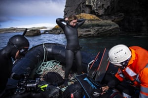Ercümen zips up her wetsuit in preparation for her first dive