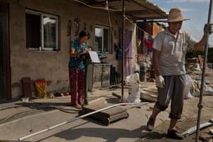 Wang Shuxia, 56 (left), from Henan, weighs scrap metal