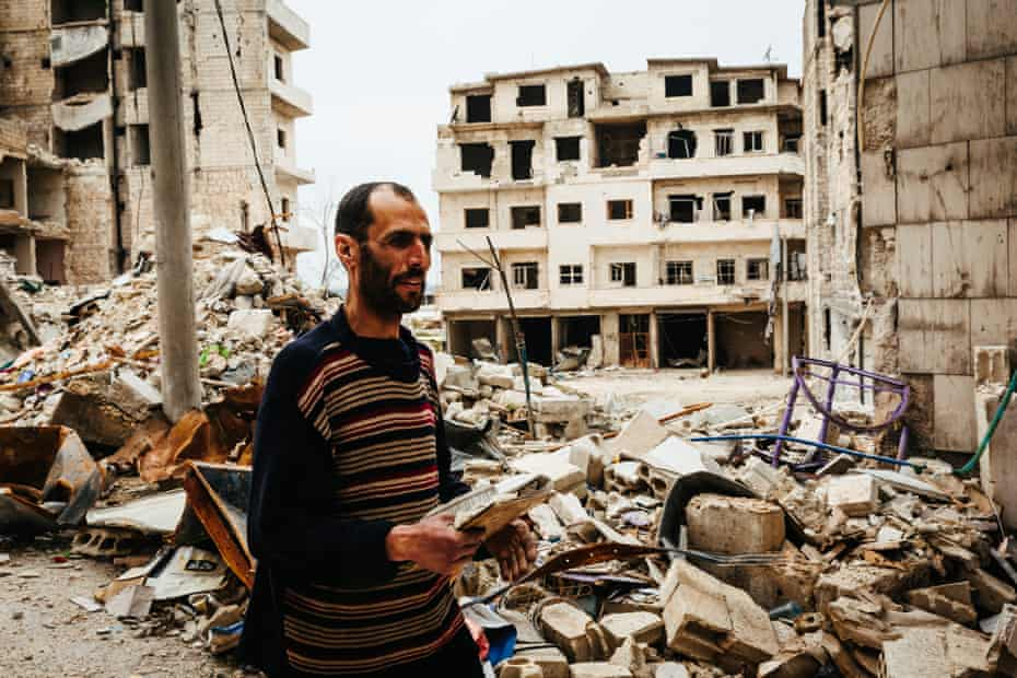 Zaqwa al-Tamer walks past a row of bombed buildings in the town of Ariha, holding pieces of a Quran he salvaged from his destroyed house.