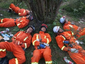 Chinese paramilitary police, exhausted from a gruelling 18-hour rescue operation in earthquake stricken Sichuan province, sleep under a tree, Jiuzhaigou, China