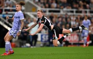 Sean Longstaff of Newcastle United is seen in midair as he watches his shot alongside Kalvin Phillips of Leeds.