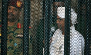 Omar al-Bashir stands in a cage at a courtroom in Khartoum