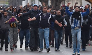 Tunisian protesters gesture towards security forces during clashes in the town of Tebourba.