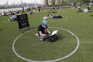 Ridley Goodside wears a mask and goggles to protect himself as he sits in a designated circle marked on the grass at Brooklyn's Domino park.