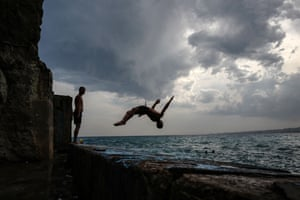 People jump into the Mediterranean in the French Riviera city of Nice.