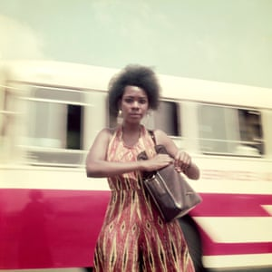 A woman stands in front of a blurred bus