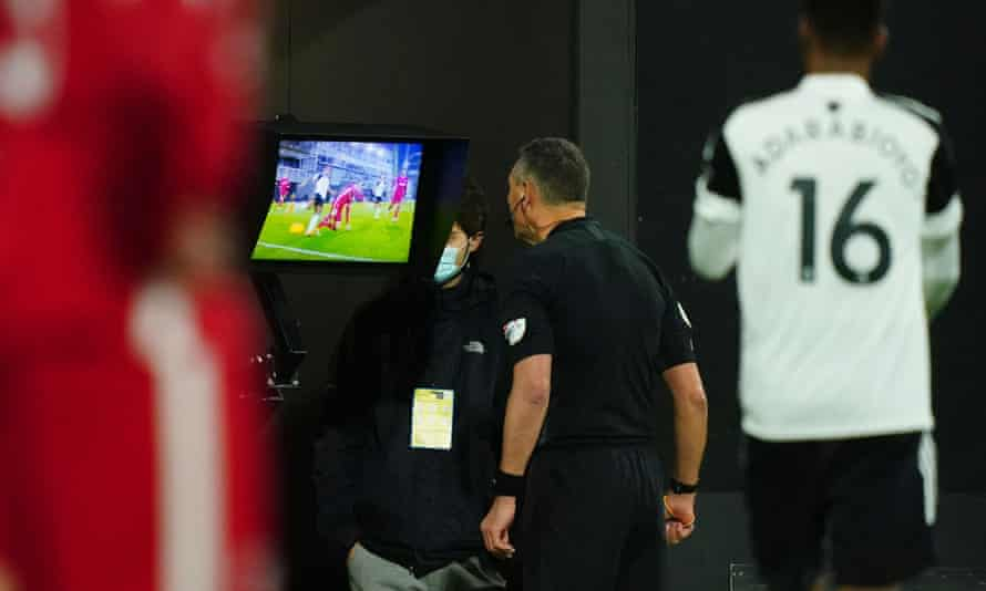 The referee Andre Marriner refers to the VAR monitor before overruling his decision to award Fulham a penalty against Liverpool last Sunday.