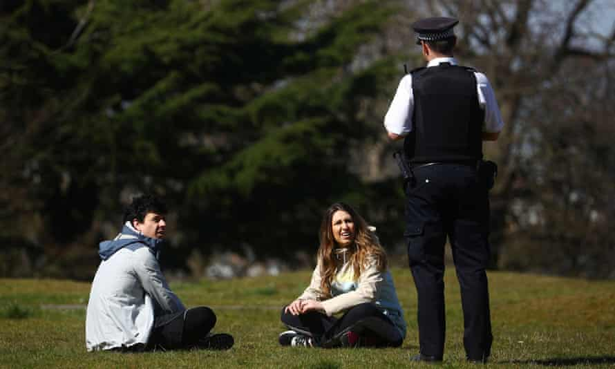 A police officer speaking to couple in Greenwich Park,