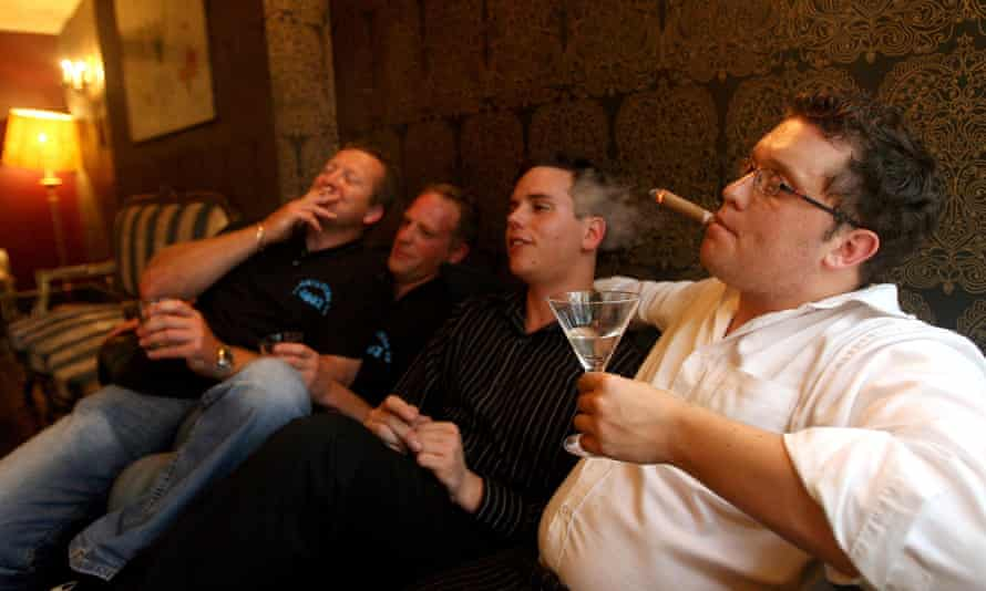a group of men smoking and drinking inside