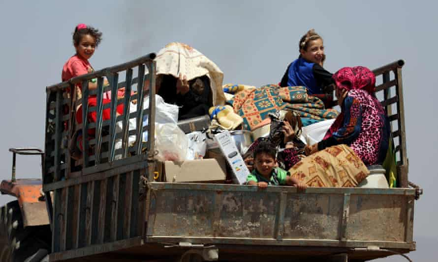 Families flee shelling near Deraa in Syria on Friday.