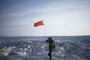 Rougeux walks after installing a flag to help identify a GPS position at the Helheim glacier.