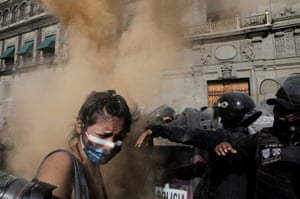 A woman reacts while clashing with police officers during a protest in support of Victoria Salazar, a Salvadoran woman who died after a Mexican female police officer was filmed kneeling on her back.