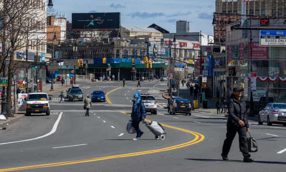 Pedestrians cross Fordham Road in the Bronx borough of New York, U.S., on Thursday, April 2, 2020. In four months, the new coronavirus infected more than 1 million people and killed more than 51,000.