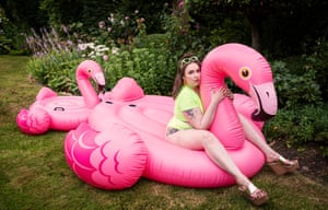 Lena Dunham photographed in Wales, July 2019, sitting on an inflatable pink flamingo