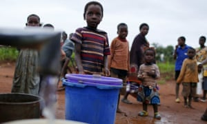 Children watch as women pump water from a borehole near Malawi's capital Lilongwe.