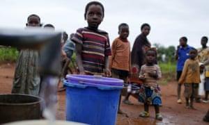 Children watch as women pump water from a borehole near Malawi's capital Lilongwe.
