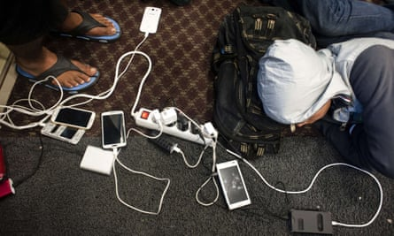 Refugees and migrants charge their mobile phones as they rest on a ferry from the Greek island of Lesbos.