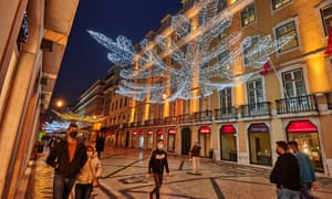Pedestrians wearing protective masks walk under the Christmas and New Year colour-changing illuminations in Rua Augusta during the COVID-19 Coronavirus pandemic on 23 November 2020 in Lisbon, Portugal.