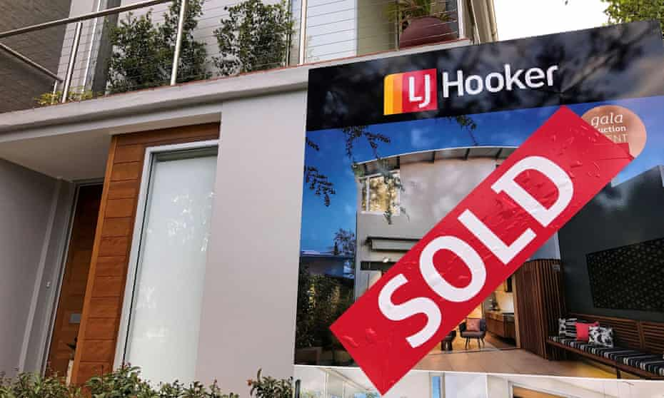 A sold sticker attached to a real estate agent's sign outside the front of a residential property in central Sydney