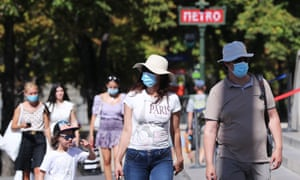 People wearing face masks walk on a street in Paris, France, 7 August 2020.