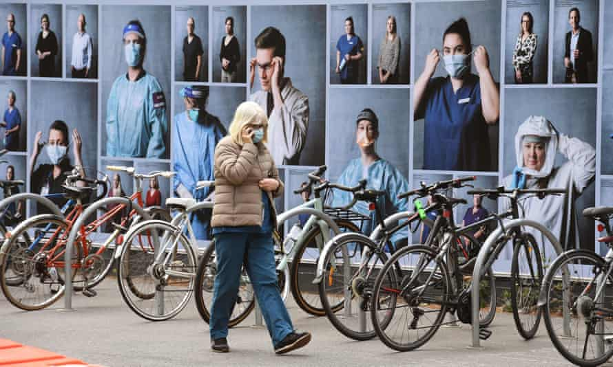 A woman walks past a display of photos outside the Royal Melbourne Hospital