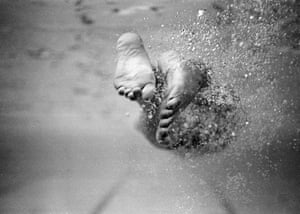 The feet of Olympic silver medal winning swimmer Bobby McGregor kick up a stream of bubbles as he makes a turn.