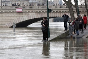 Residents stand by the swollen waters of the Seine