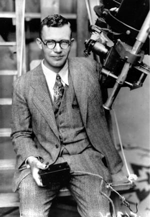 In this 1931 photo Clyde Tombaugh poses with the telescope through which he discovered Pluto at the Lowell Observatory in Flagstaff, Arizona.<br>