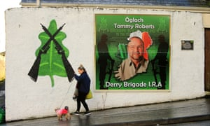 A woman and her dog walk past an Irish republican mural in Derry