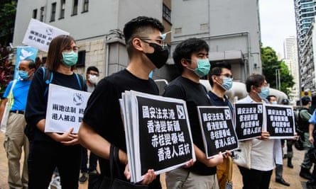 Pro-democracy protesters hold placards as they march in Hong Kong on 22 May.