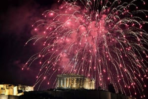 Fireworks explode by the Ancient Acropolis in Athens during the New Year celebrations