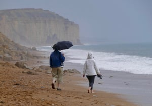 While the majority of Britain basks in sunshine, people in West Bay, Dorset, make the best of the heavy rainfall